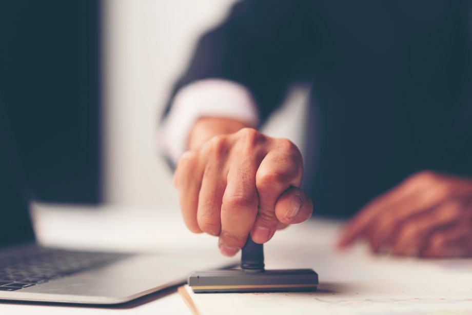 Ein Geschäftsmann drückt einen Stempel auf ein Dokument.