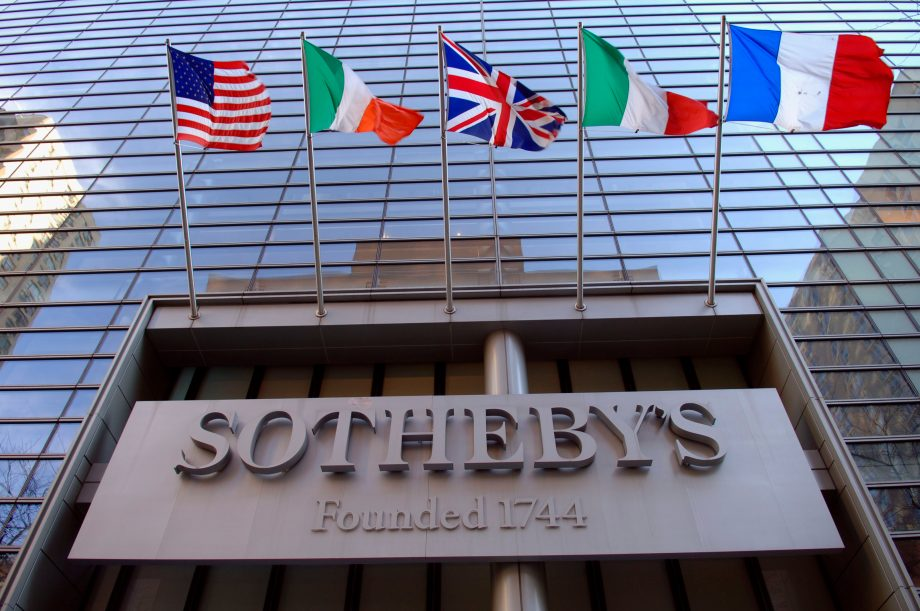 Das Sotheby's-Logo prangt an einer gläsernen Fassade. Darüber wehen die Flaggen der USA, Italiens, Großbritanniens, Irlands und Frankreichs.
